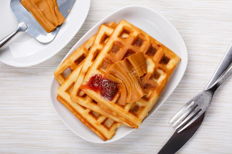 Norwegian brunost on white table. Homemade waffles with Scandinavian brown cheese and strawberry jam stock photos