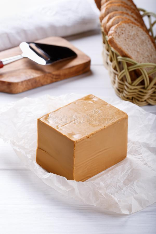 Norwegian brunost on white table. Traditional Scandinavian brown cheese royalty free stock images