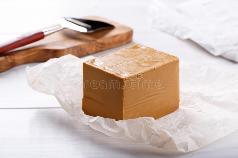 Norwegian brunost on white table. Traditional Scandinavian brown cheese stock photography