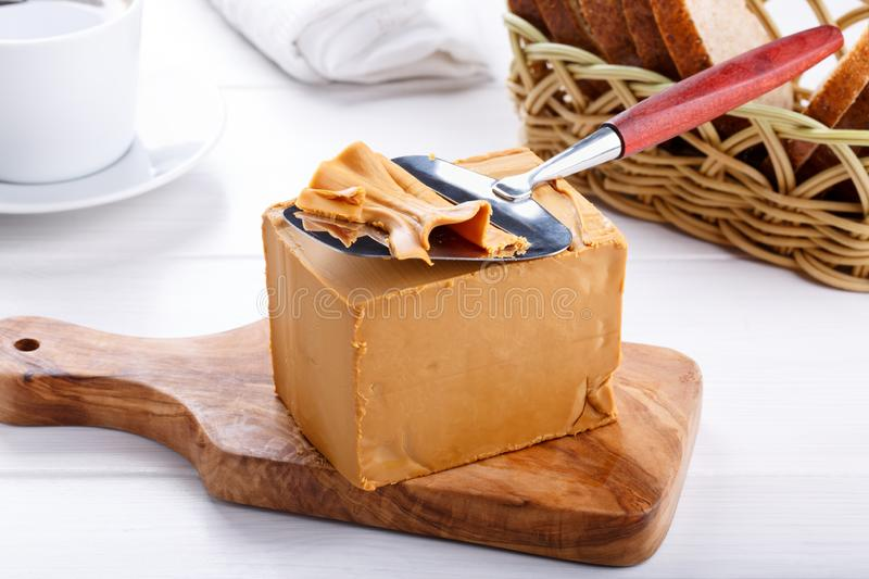 Norwegian brunost on white table. Traditional Scandinavian brown cheese stock photo