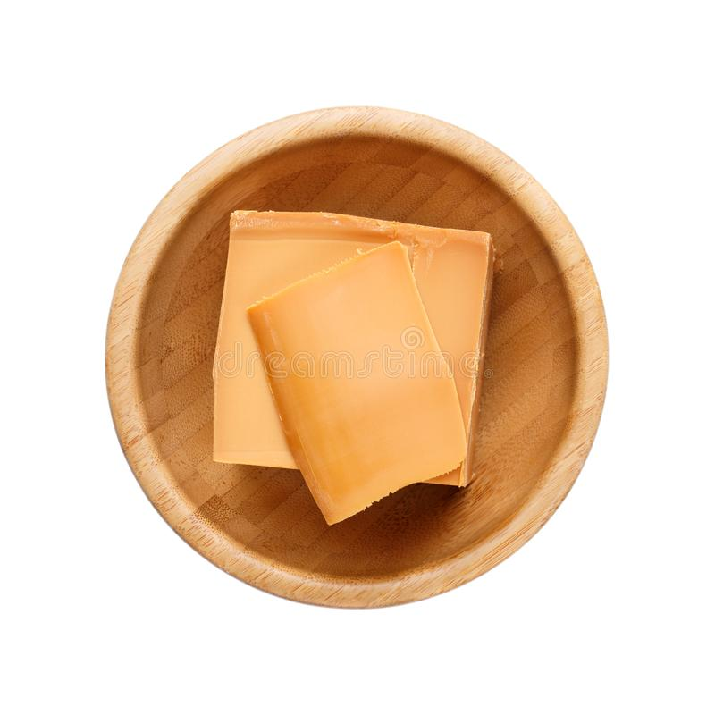 Norwegian brunost in wooden bowl Isolated on white. Traditional Scandinavian brown cheese. Top view stock images