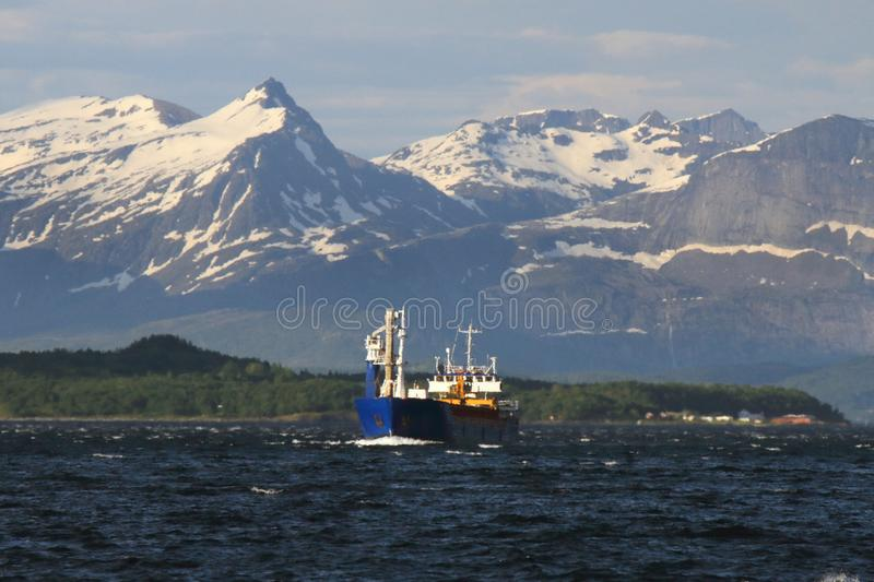 Norwegian cargo ship facing the mountains of Meløy. Norwegian cargo ship leaving Meløy fjord, Nordland County Arctic Norway stock images