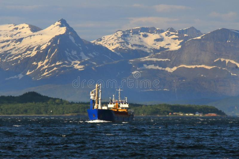 Norwegian cargo ship leaving Meløy. Fjord, Nordland County Arctic Norway stock photography
