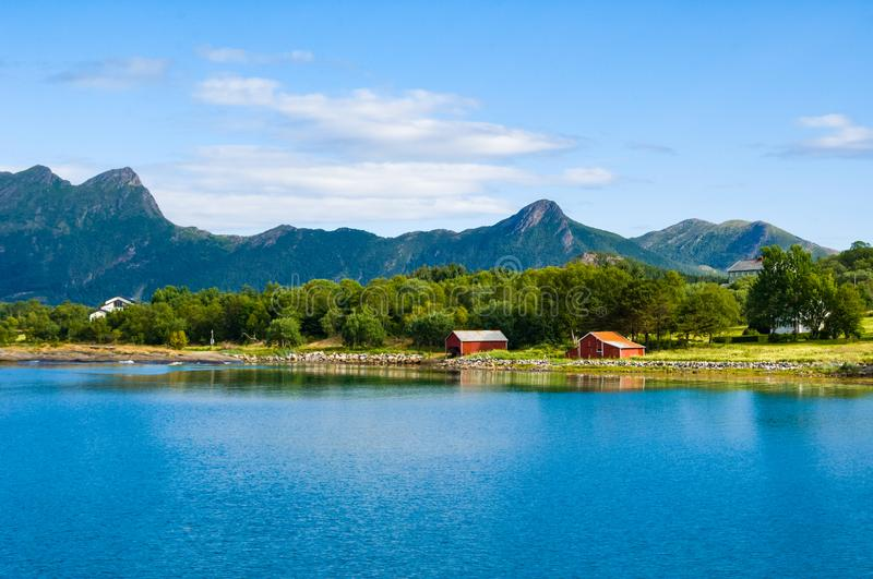 Norwegian coast, typical landscape at Norwegian coastline with mountains in back and small red houses on shore royalty free stock image