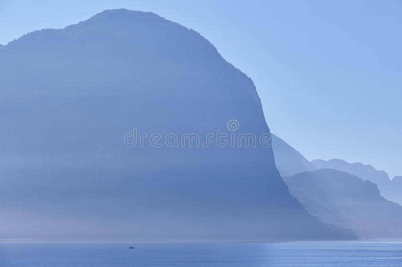 Norwegian fjord landscape sunrise in blue tone. Fisheman solitude. royalty free stock photography