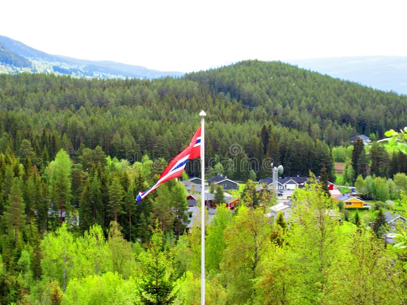 The Norwegian flag in a pennant whit a bit of village in background stock photography