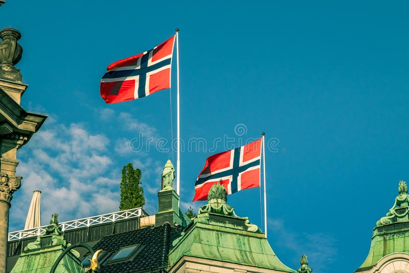 Norwegian flags. Two Norwegian flags are flying at the top of a building in Oslo royalty free stock images