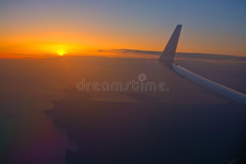 Norwegian flight image at sunrise in the ocean beyond Menorca. MALLORCA, SPAIN - APRIL 27, 2018: Norwegian flight image at sunrise in the ocean beyond Menorca in royalty free stock photo