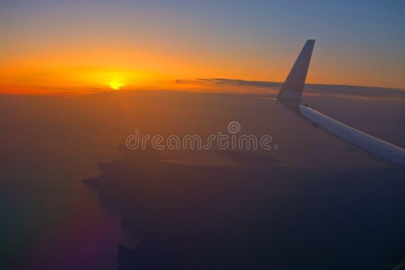 Norwegian flight image at sunrise in the ocean beyond Menorca. MALLORCA, SPAIN - APRIL 27, 2018: Norwegian flight image at sunrise in the ocean beyond Menorca in royalty free stock images
