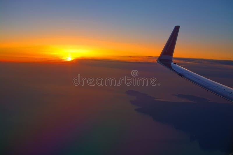 Norwegian flight image at sunrise in the ocean beyond Menorca. MALLORCA, SPAIN - APRIL 27, 2018: Norwegian flight image at sunrise in the ocean beyond Menorca in royalty free stock photography