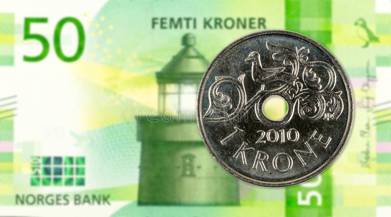 1 norwegian krone coin against 50 new norwegian krone banknote stock photo