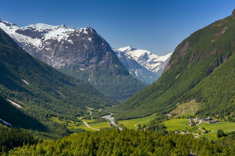 Norwegian green valley. Norwegian landscape with green valley and small village between mountains with snow peaks. Nature and travel background. Jostedalsbreen stock photos