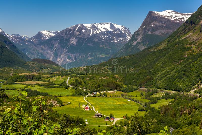 Norwegian green valley. Norwegian landscape with green valley and small village between mountains with snow peaks. Nature and travel background. Jostedalsbreen royalty free stock image