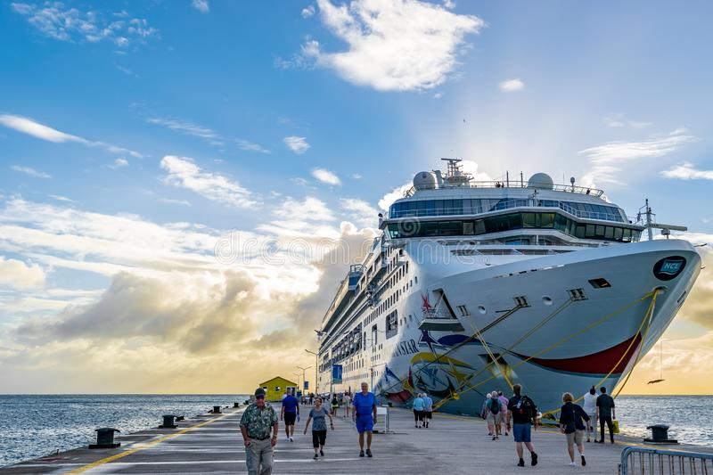 Norwegian NCL Star Cruise Ship docked at the Phillipsburg Cruise Port Terminal in Sint Maarten. Arriving passengers walking on t stock photos