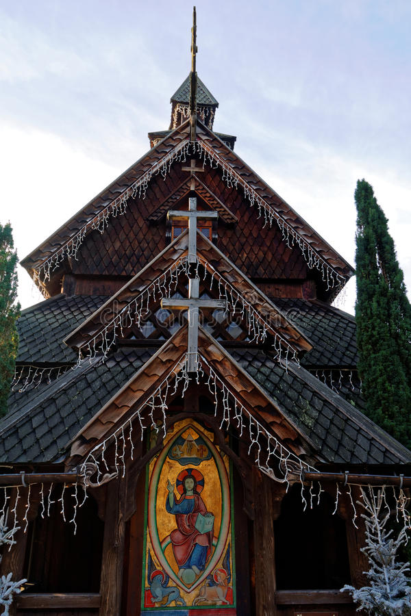 Norwegian stave church replica at Christmas. A medieval wooden church building decorated with fairy lights in Christmas season. Replicated and on display in stock photo