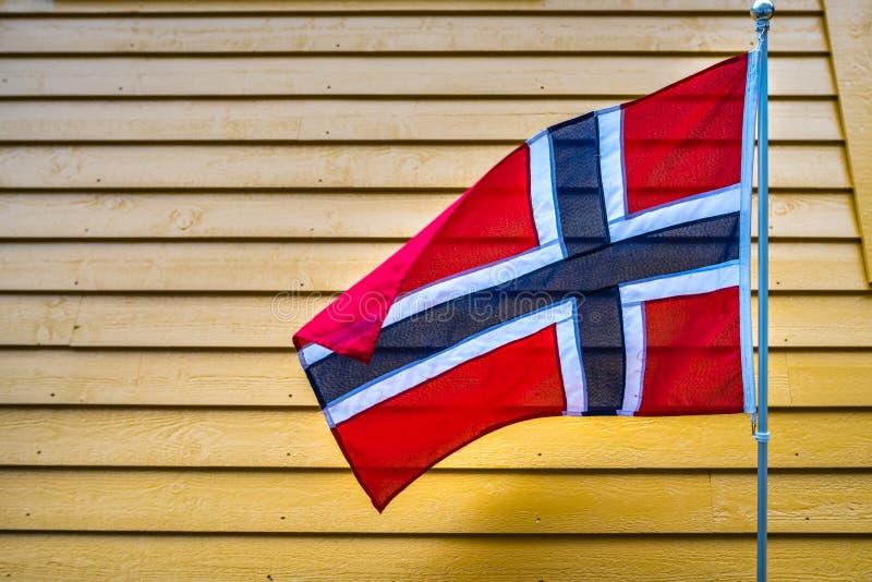 Norwegische Flagge über gelbem hölzernem Wandhintergrund stockbilder