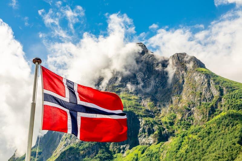 Norwegische Staatsflagge, die in den Wind und in das mountain& x27 wellenartig bewegt; s-Spitze in Neroy-Fjord, Aurlan, Sogn-og F lizenzfreie stockfotos