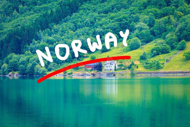 Norwescy dom na wsi w górach na jeziornym brzeg fotografia royalty free