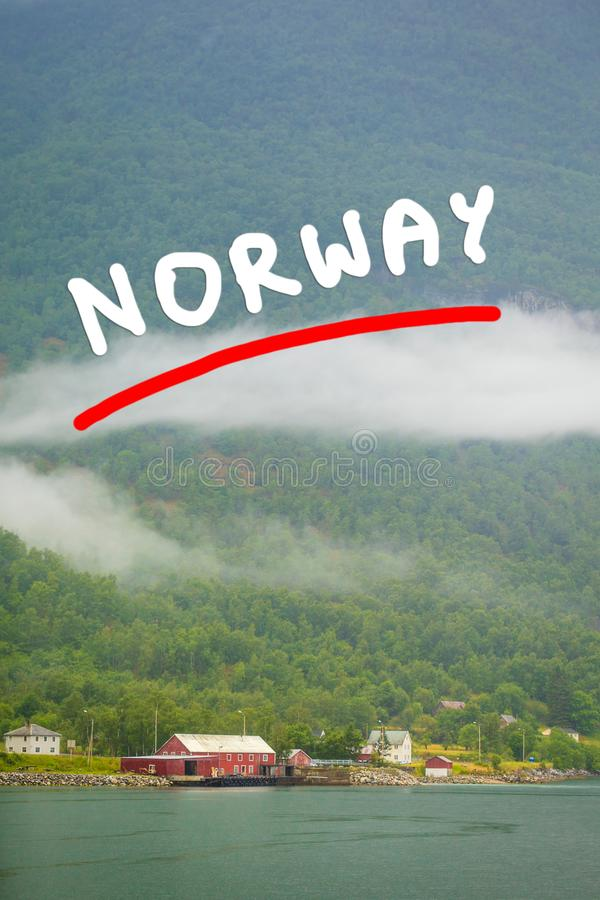 Norwescy dom na wsi w górach na jeziornym brzeg zdjęcie stock