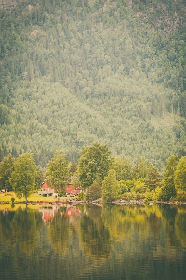 Norwescy dom na wsi w górach na jeziornym brzeg obraz stock