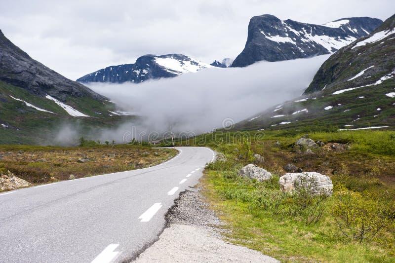 Norweska asfaltowa droga z unosić się chmurę między górami na drodze Trollstigen, Norwegia obraz stock