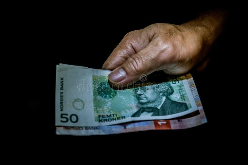 Norweskich Kroner rachunki w ręce osoba odizolowywająca na czerni obraz stock