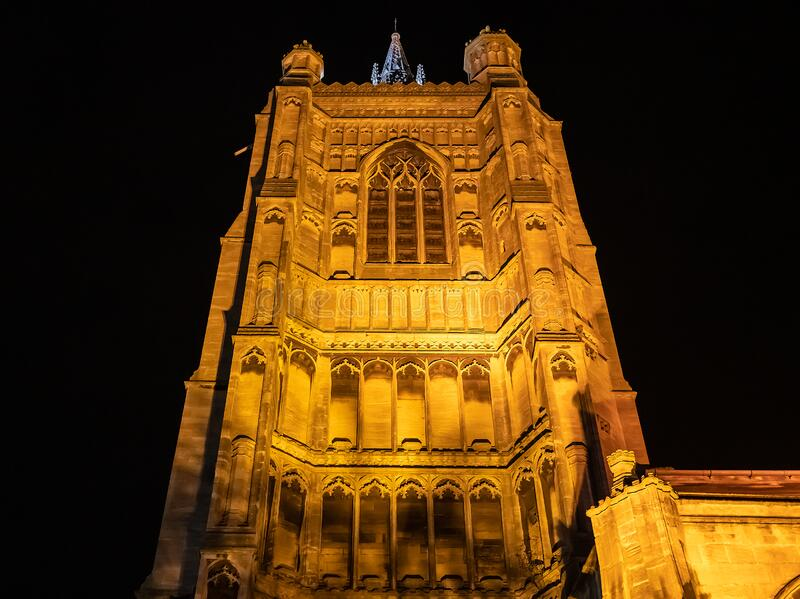 Norwich cathedral spire illuminated at night. Looking upwards at an illuminated church spire against a black sky royalty free stock photo