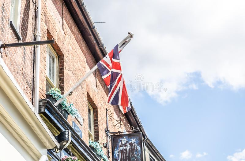 Flag of the United Kingdom hanging on a brick facade of a typical English building. NORWICH, ENGLAND - JULY 8: Flag of the United Kingdom hanging on a brick royalty free stock photography