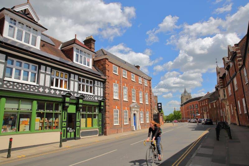 NORWICH, UK - CZERWIEC 4, 2017: Młody rudzielec kobiety kolarstwo na Bethel ulicie z domami i pięknym niebem kolorowymi i średnio obrazy royalty free