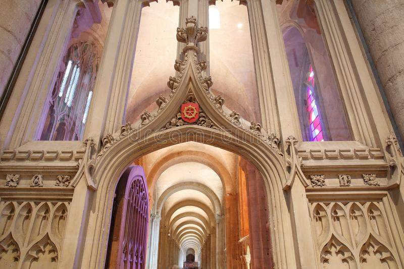 Trinity Windows with bright colors inside the Cathedral, viewed through an arch with carvings royalty free stock photo