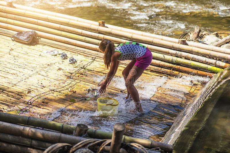 Nos bancos da menina do rio que mant?m peixes travados no rio Meninas em um peixe da captura do dia de ver?o no rio imagem de stock royalty free