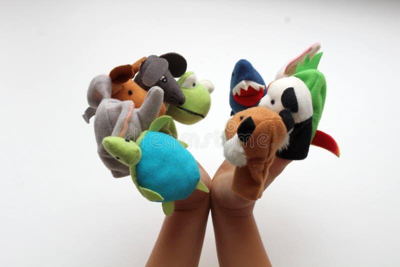 Nos dedos pequenos do bebê, os brinquedos macios jogam animais em um teatro do fantoche fotografia de stock royalty free