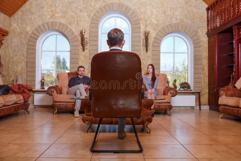Nos pares de Young do psicólogo que sentam-se no sofá, resolva o problema, doutor que senta-se na cadeira que escuta eles imagens de stock