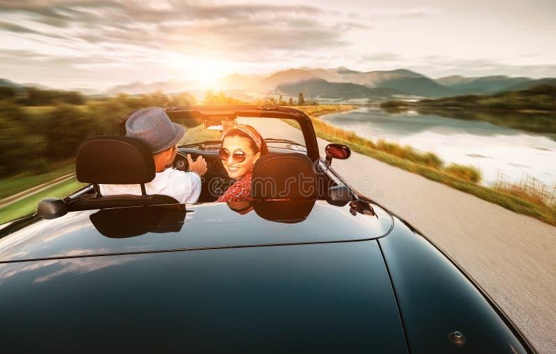 Nos pares do amor que viajam pelo carro do cabriolet imagens de stock