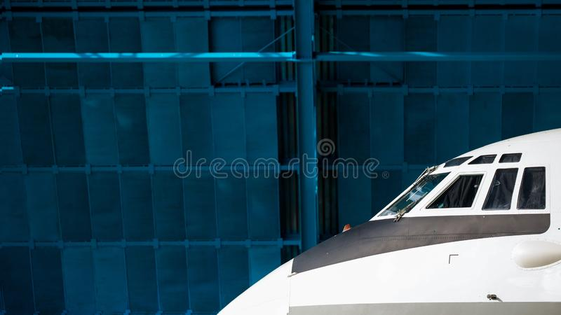 The nose of the aircraft against the blue hangar. Front portholes.  stock photos