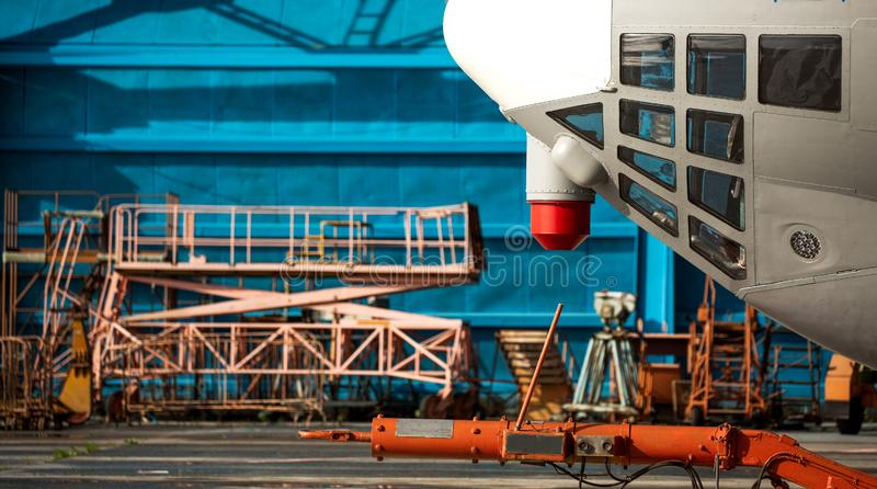 The nose of the aircraft against the blue hangar. mobile ladders, lower observation windows.  royalty free stock photos