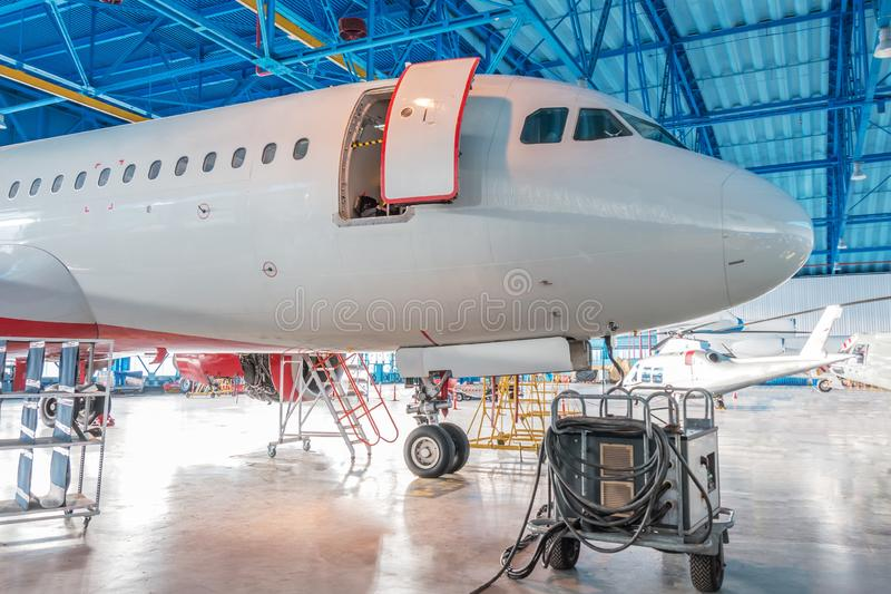 The nose of the aircraft fuselage with open door in the aircraft hangar.  royalty free stock image