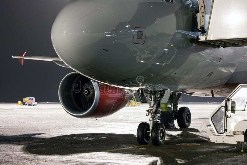 Nose, engine and landing gears of passenger airplane at the night airport apron royalty free stock photography