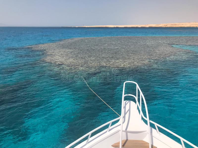 The nose, the front of the white yacht, the boat, the ship standing on the jig, parking, anchoring in the sea, the ocean with blue. Water with coral reefs stock images