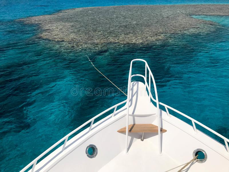 The nose, the front of the white yacht, the boat, the ship standing on the jig, parking, anchoring in the sea, the ocean with blue. Water with coral reefs royalty free stock images