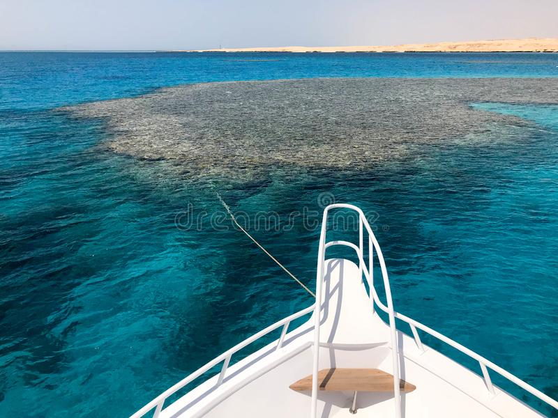 The nose, the front of the white yacht, the boat, the ship standing on the jig, parking, anchoring in the sea, the ocean with blue. Water with coral reefs stock image