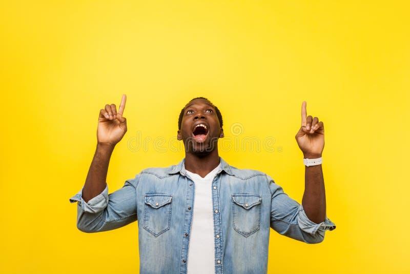 Nossa, anuncie! Retrato de um homem feliz surpreso apontando para cima foto de estúdio isolada em fundo amarelo imagens de stock