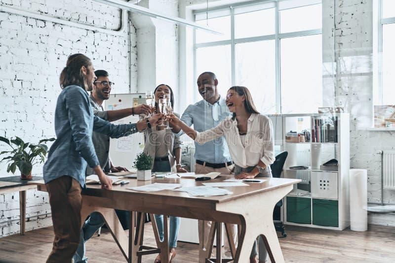 A nossa equipe! Grupo de executivos felizes que brindam-se foto de stock