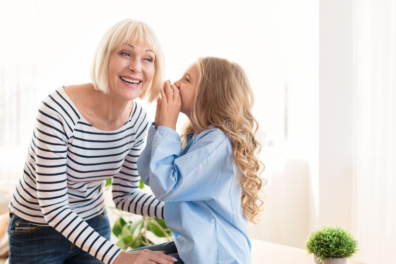 Nosso segredo Menina adorável que sussurra à avó imagens de stock