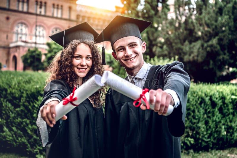 Nossos pais são tão orgulhosos de nós Os graduados felizes estão estando na universidade exterior nos envoltórios com diplomas à  imagem de stock royalty free
