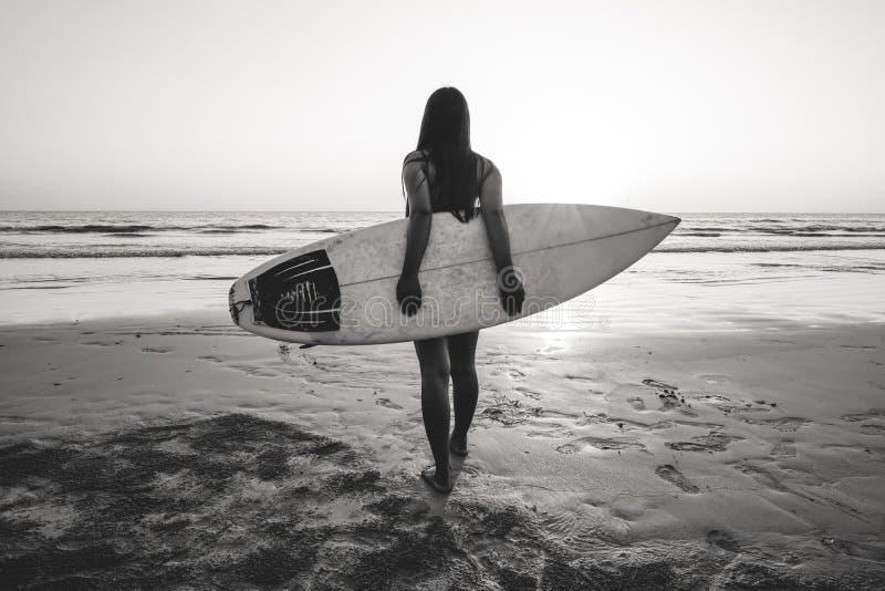 Nostalgi- och minnefoto av surfarekvinnan i bikini att gå till att surfa royaltyfri fotografi