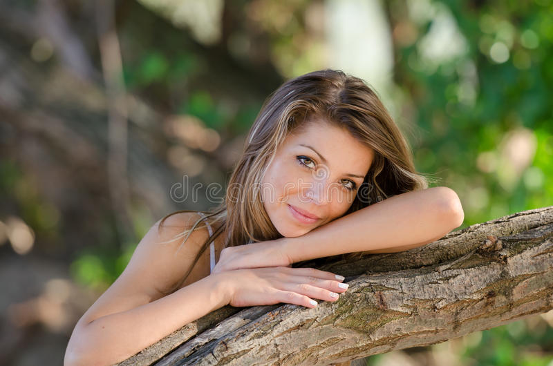 Nostalgic moments of a beautiful girl as she rests on a tree trunk royalty free stock photo