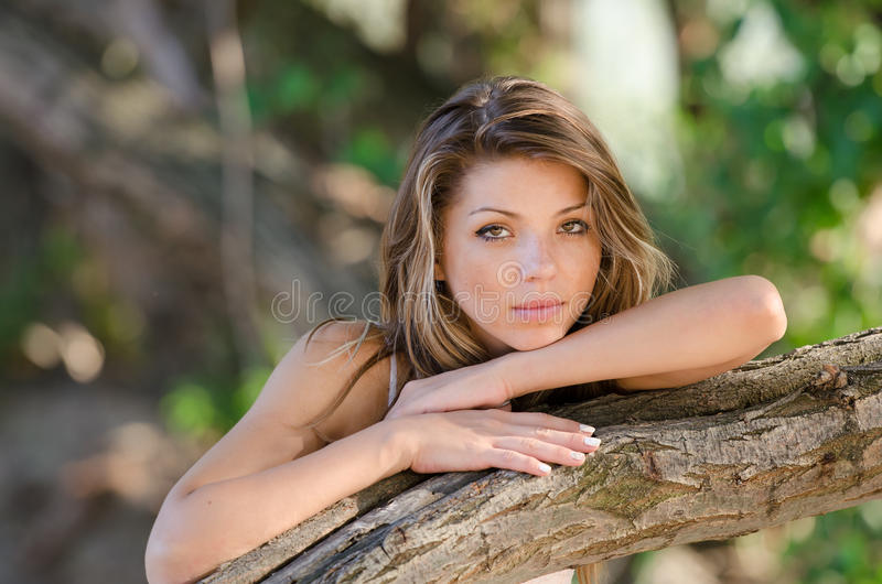 Nostalgic moments of a beautiful girl as she rests on a tree trunk stock photos