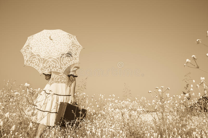 Nostalgic old photo in sepia color. Girl with her umbrella walking alone and searching her way. Old photo in sepia color. Girl with her umbrella walking alone stock photos