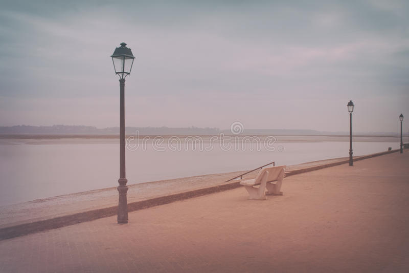 Nostalgic promenade. Empty boardwalk in winter at the Somme Bay, Le Crotoy romantic nostalgic filter stock images